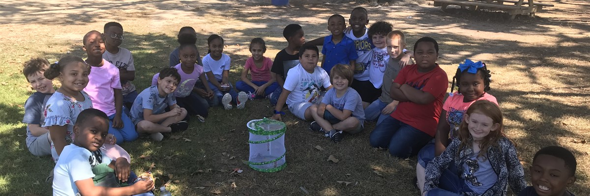 JWE 2nd grade students release butterflies after raising caterpillars and observing life cycle stages in class.